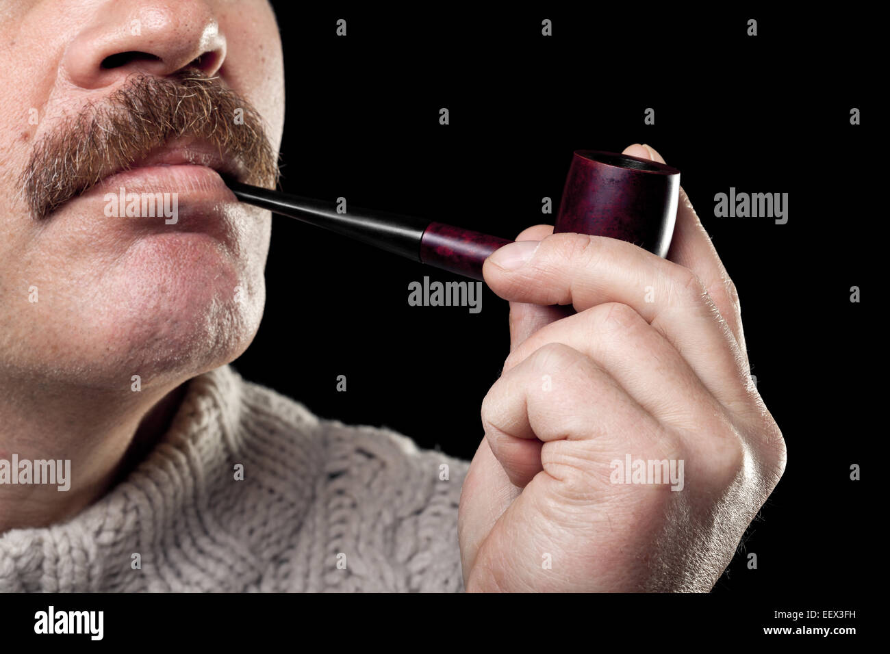 mature caucasian man holding smoking pipe in hand isolated on black background - Stock Image