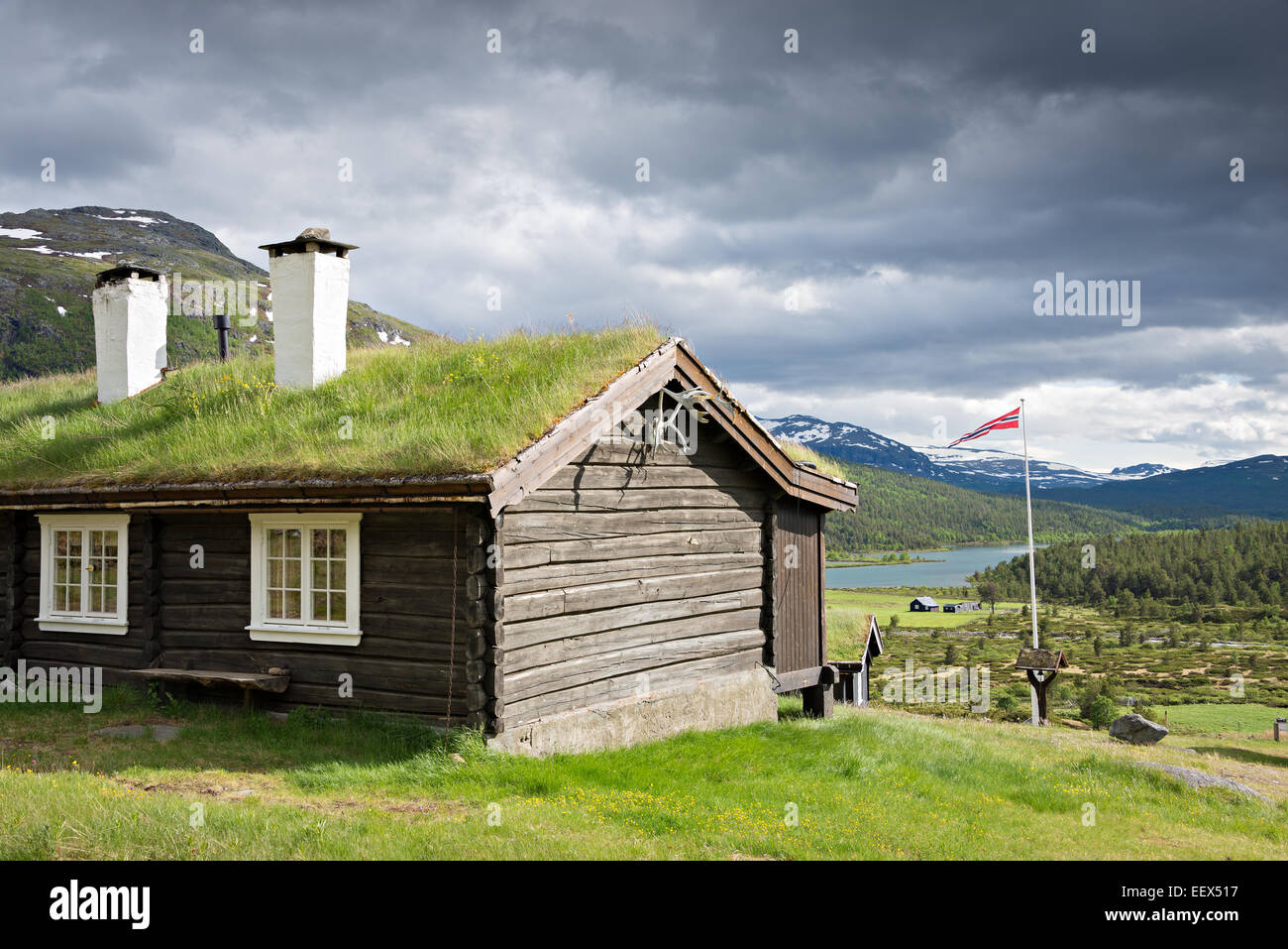 A sod roof log cabin with grass on top and two chimneys with a view over a lake in a valley in Jotunheimen national - Stock Image