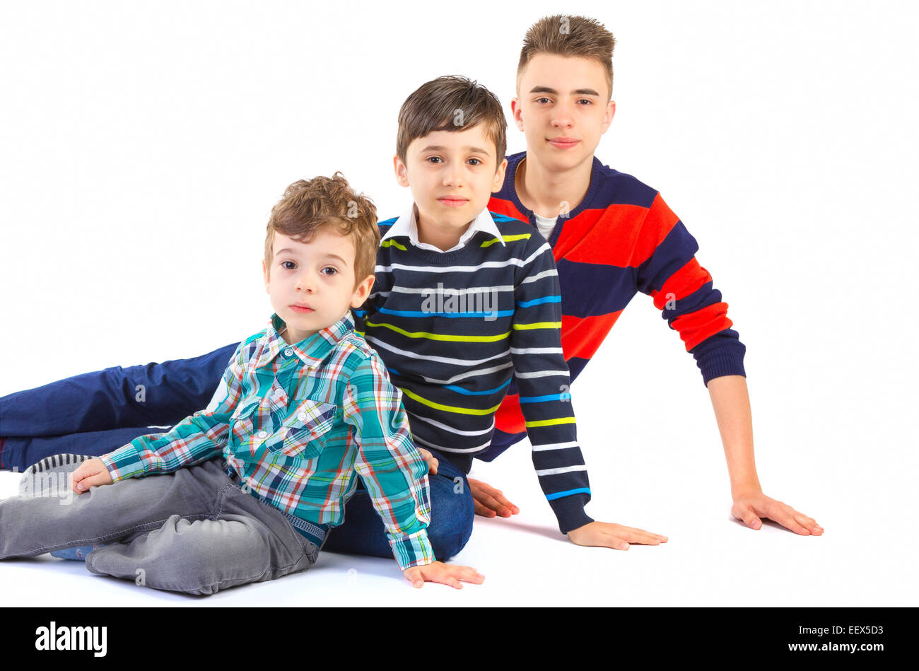 Shot studio with three brothers on white background - Stock Image