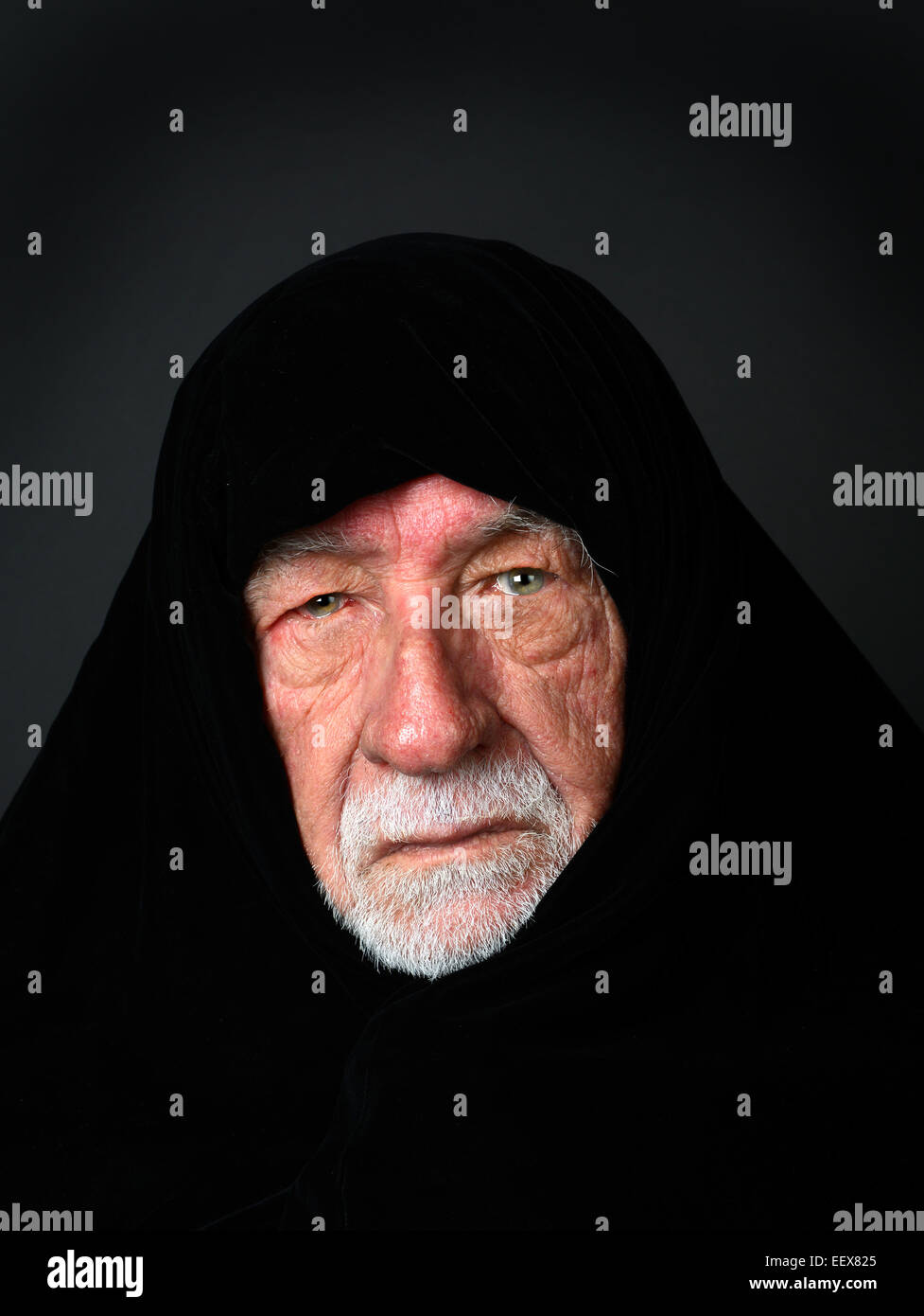 Elder Arab Sheik with a somber expression with a black headdress looking directly into the camera - Stock Image