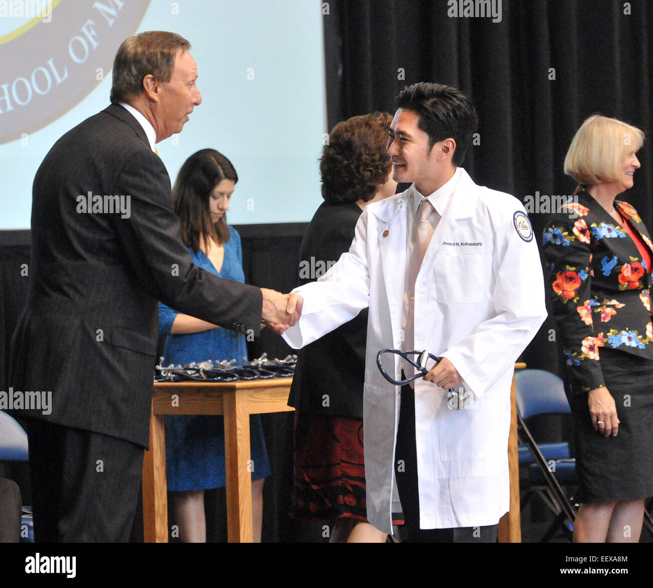 Hamden CT USA Edward Kobayashi gets a handshake from Quinnipiac University president John Lahey after being cloaked. - Stock Image