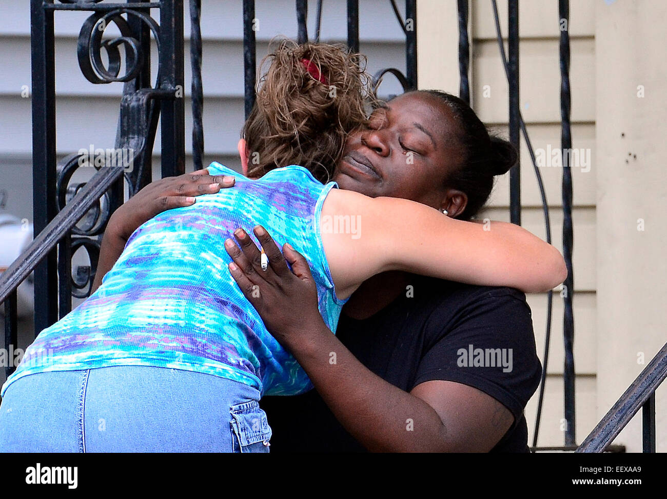 A relative of the shooting victim, right, gets consoled by a neighbor outside the house at 127 Clay Street, the - Stock Image