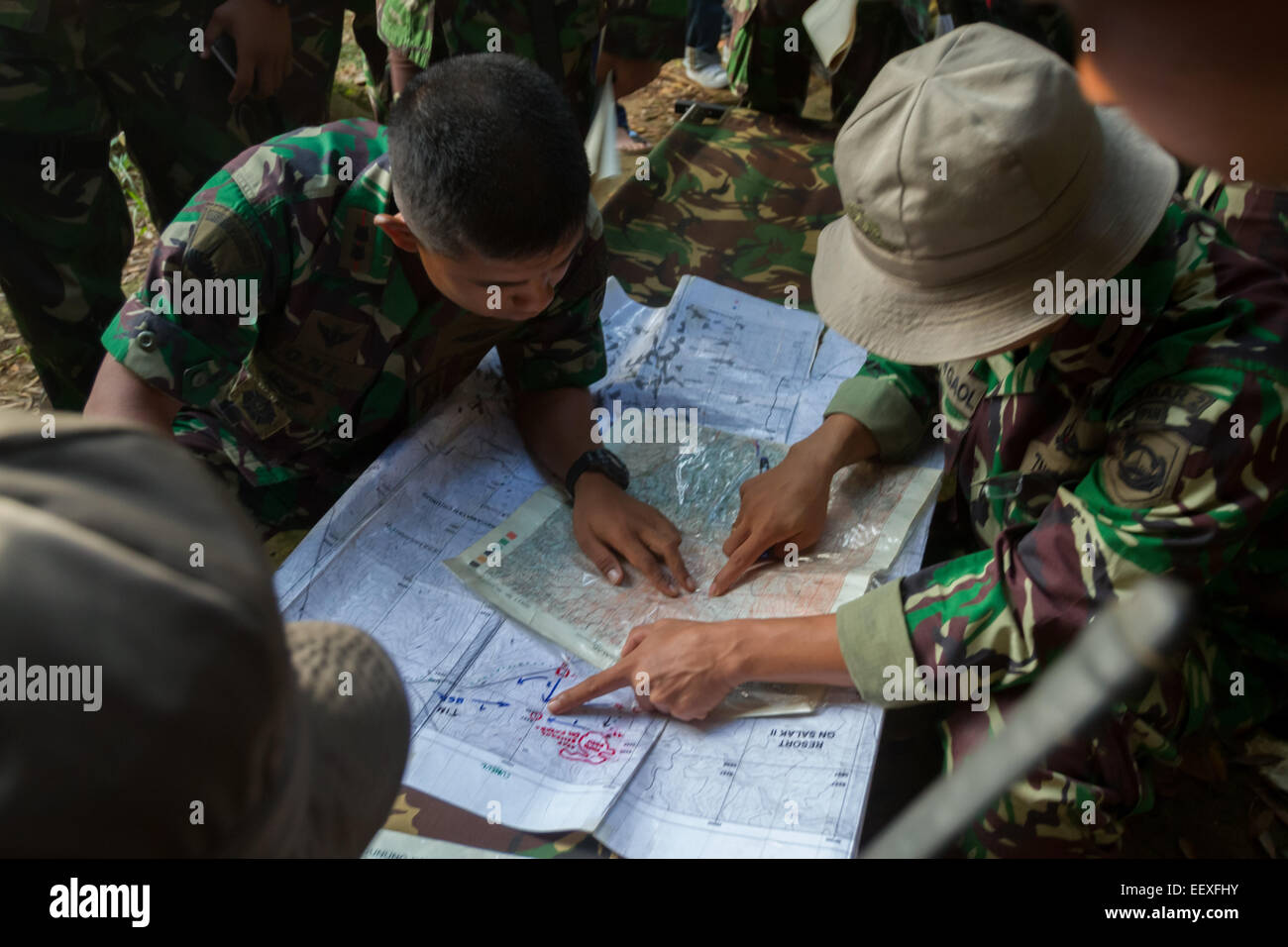 Indonesian marines plotting the Sukhoi Superjet 100 crash site on map in Mount Salak region, a day after the accident. - Stock Image