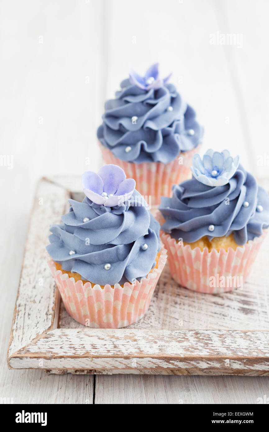 Three purple cupcakes with buttercream frosting swirl, silver pearls and edible flowers - Stock Image