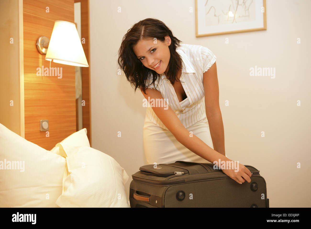 Reisevorbereitung, Frau, Bett, Koffer, packen, Reissverschluss, schliessen, Reisevorbereitungen, Kofferpacken, einpacken, Stock Photo
