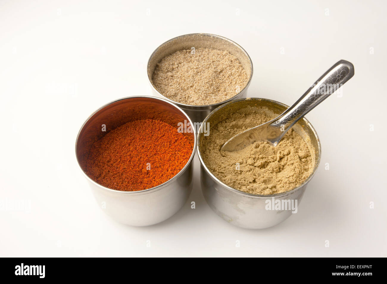Stainless Steel Pots of Ground Chilli Corinader and Ginger with a Measuring Spoon - Stock Image