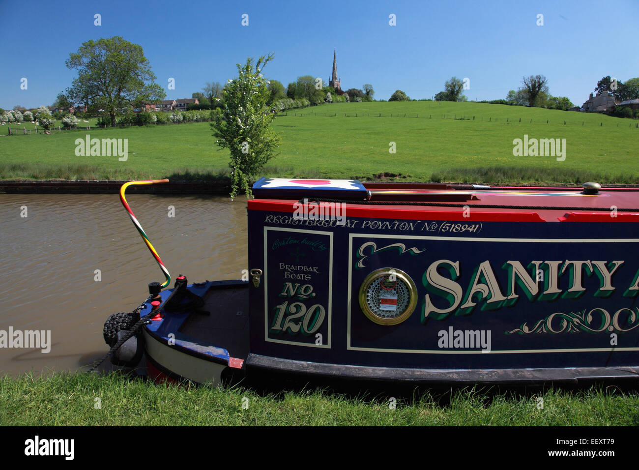 Narrowboat moored on the Oxford Canal at Braunston with the village church in the background - Stock Image