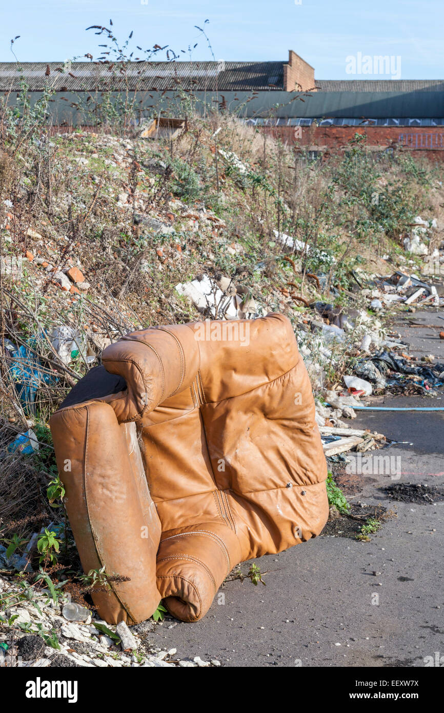 Fly tipping. Illegal dumping of a leather armchair, waste and other rubbish on a pavement on the outskirts of a - Stock Image
