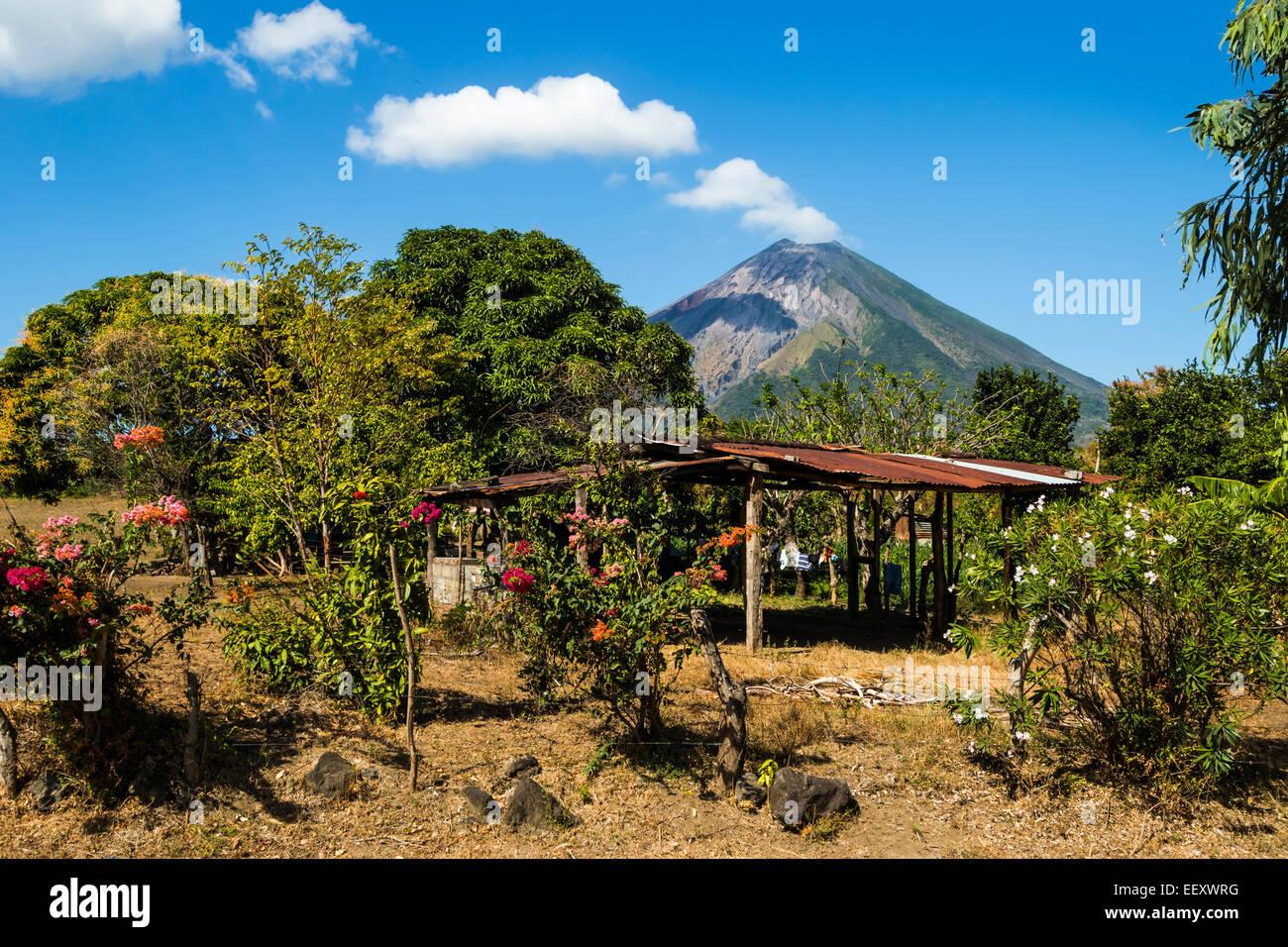 Simple home with 1610m active Volcan Concepcion beyond, near Moyogalpa; Omotepe Island, Lake Nicaragua, Nicaragua Stock Photo