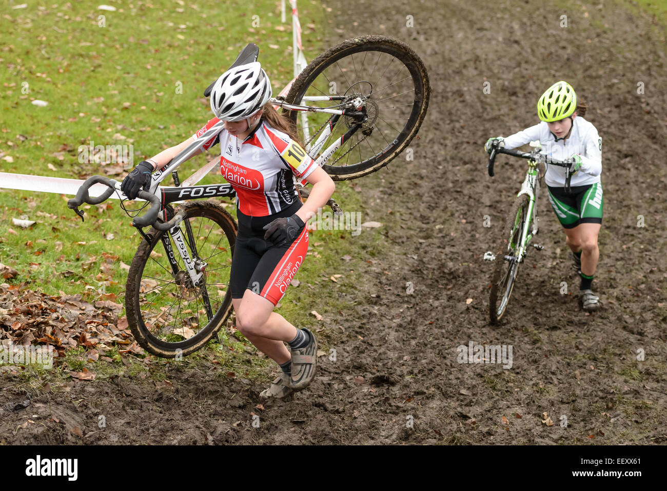 Two young female competitors tackle a steep muddy hill incline at a cyclo-cross cyclocross event. - Stock Image