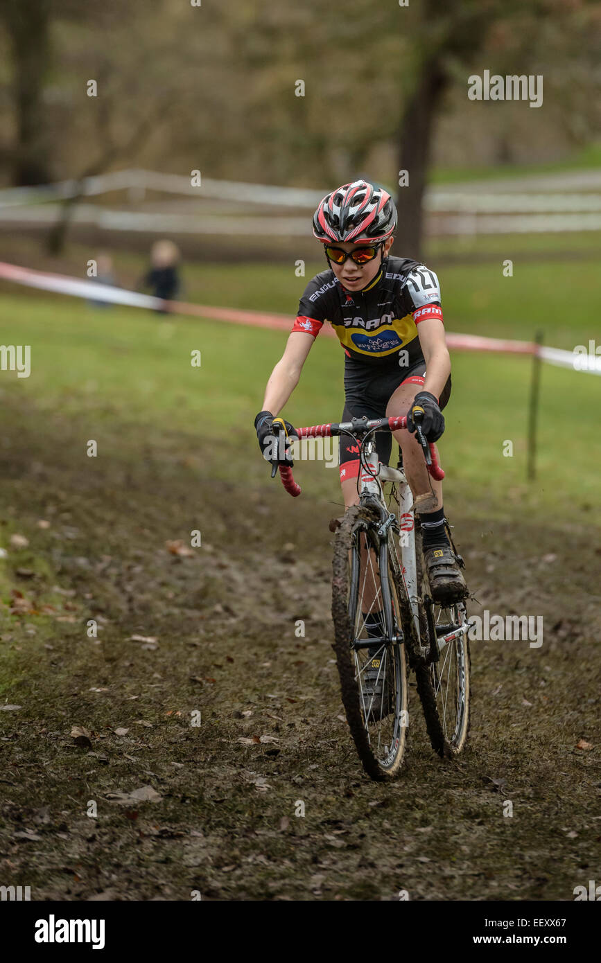 A young male competitor rides his bike through a muddy section of a British cyclo-cross race. - Stock Image