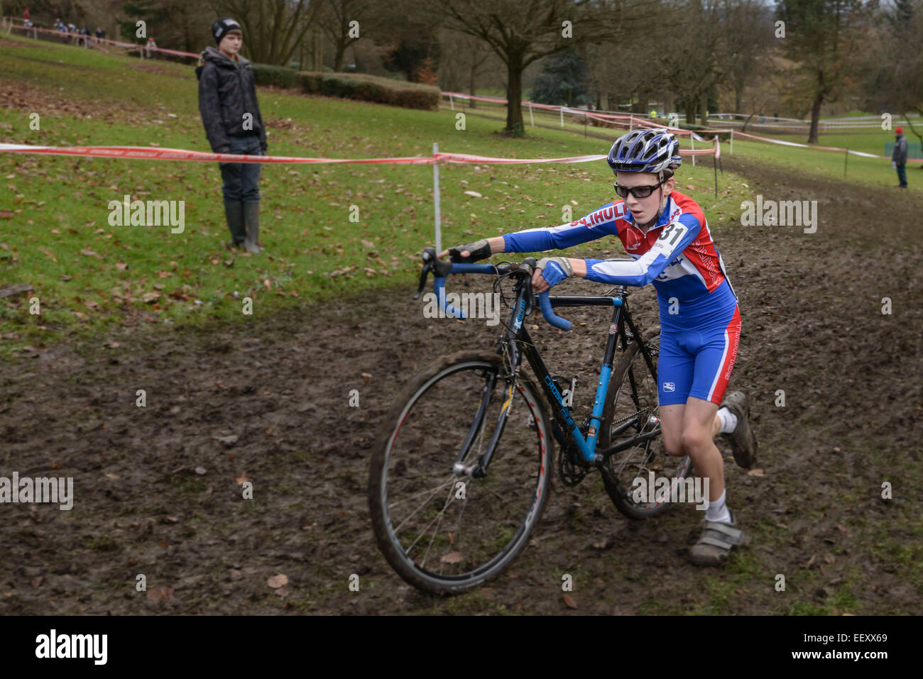 A young male competitor pushes his bike through a muddy section during a cyclo-cross race. Horizontal format with - Stock Image