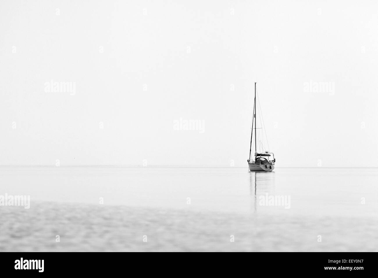 A sailing boat resting anchored on a calm sea - Stock Image