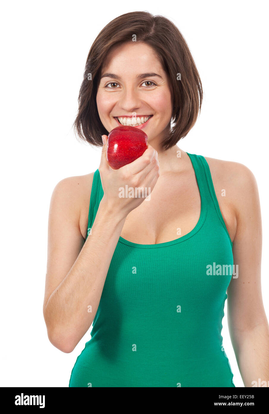 Beautiful young brunette eating a red apple, isolated on white - Stock Image