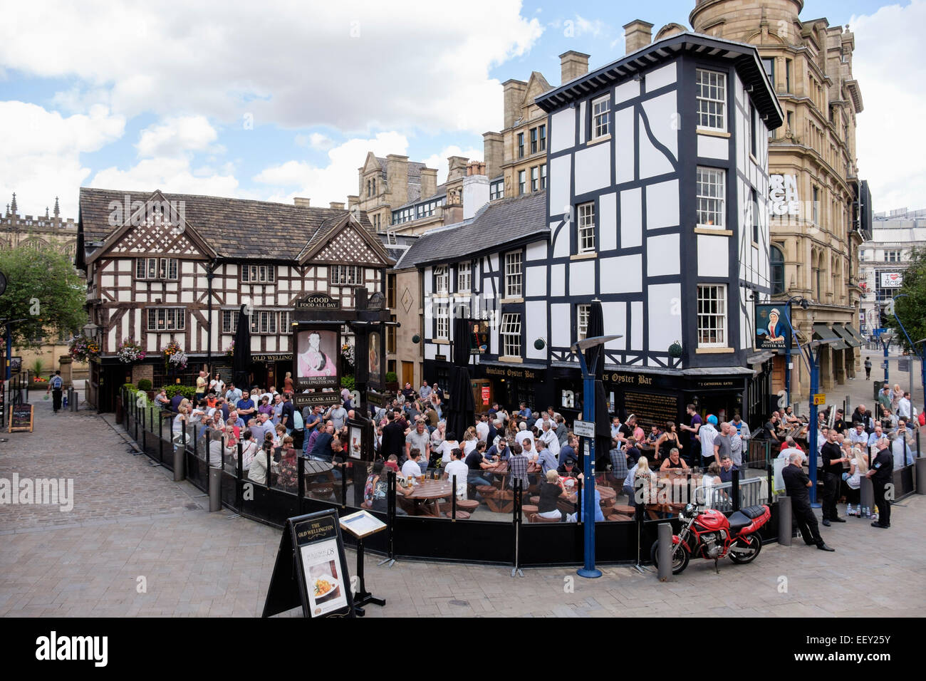 Busy 16th century timbered The Old Wellington Inn 1552 urban pub with a crowd of people in beer garden. Manchester, - Stock Image