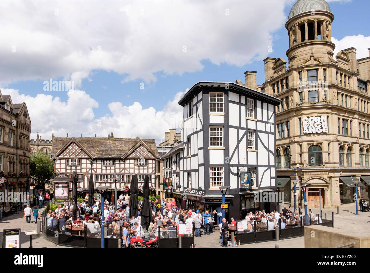 16th century timbered The Old Wellington Inn 1552 timbered building with crowds of people in beer garden. Manchester - Stock Image