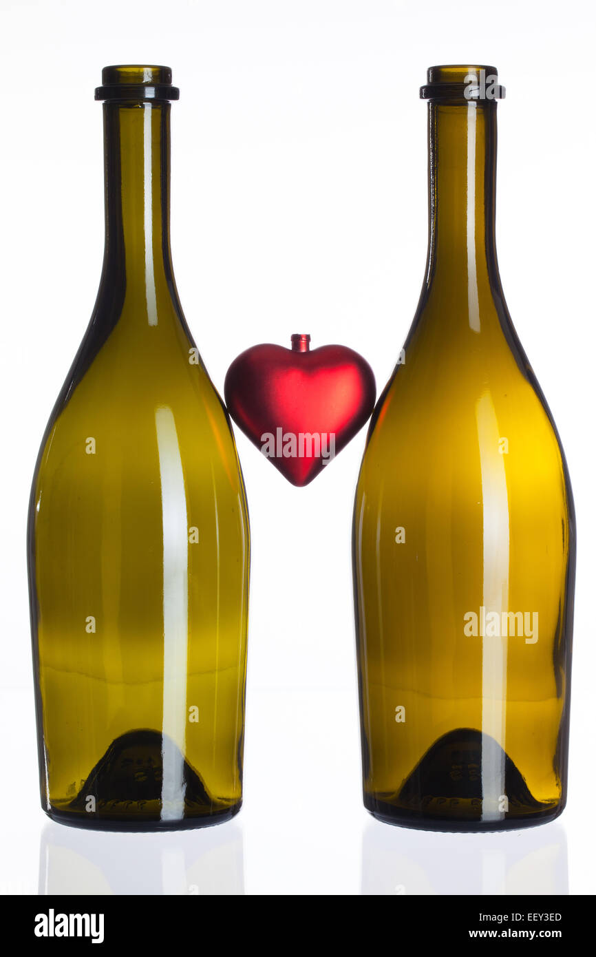 Empty bottles of wine and red heart on a glass table Stock Photo