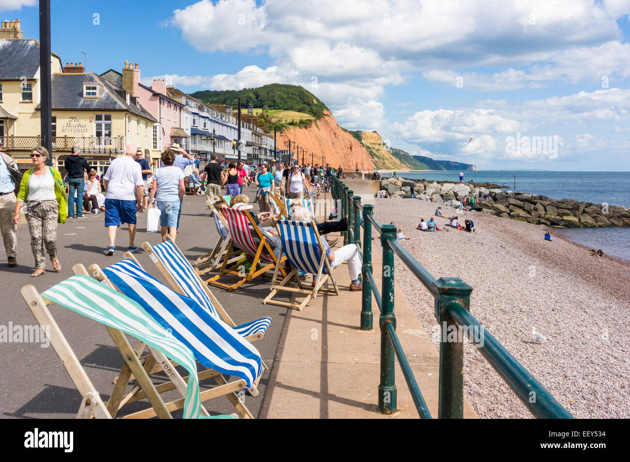 Deckchairs on the promenade at Sidmouth, East Devon, England, seaside UK in summer - Stock Image