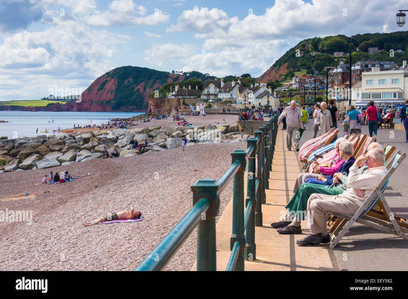 People sitting in deckchairs on the seafront at Sidmouth, East Devon, England, UK - Stock Image