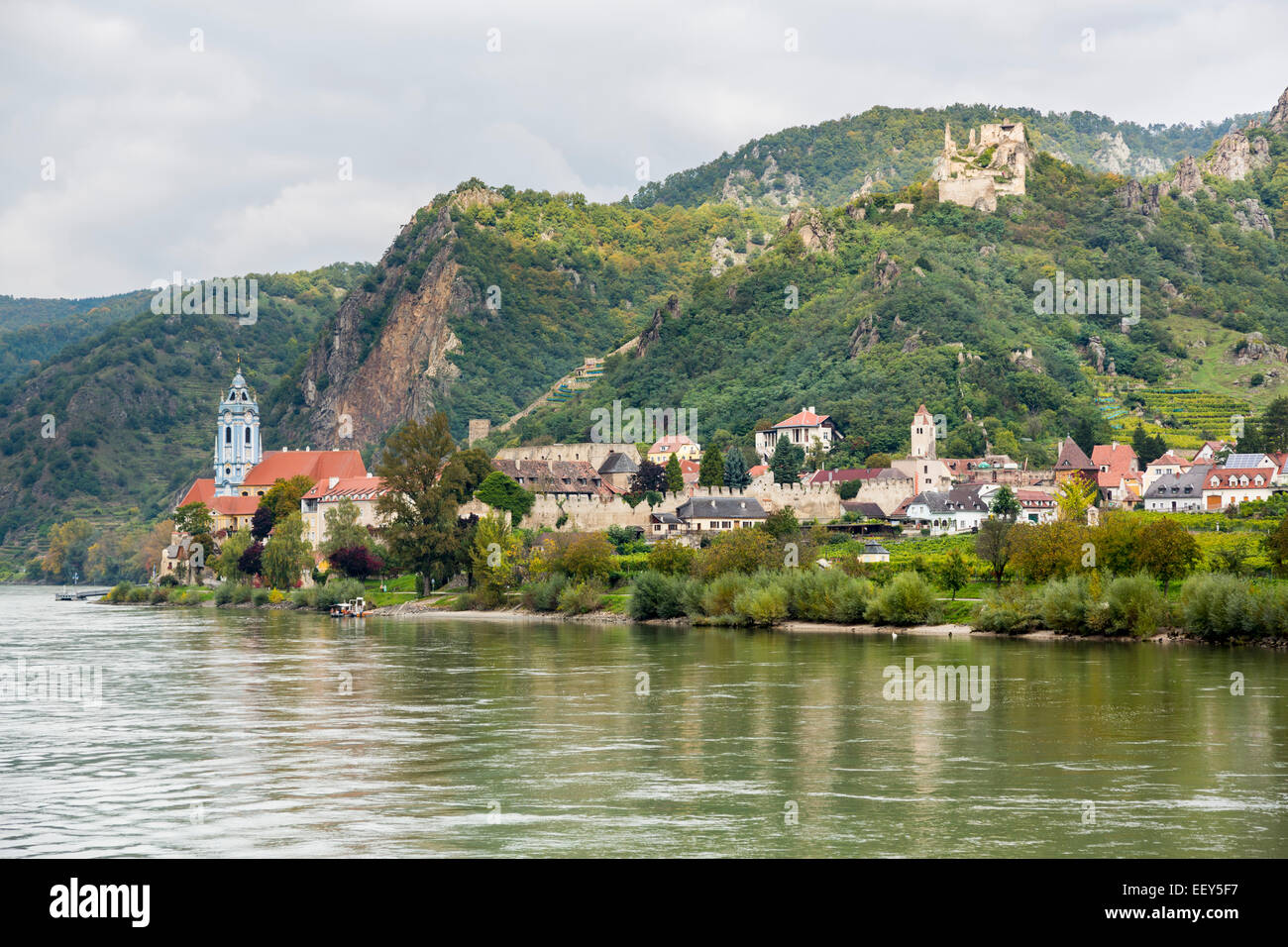 Ornate church, hilltop castle and buildings on banks of River Danube in Durnstein, Austria - Stock Image