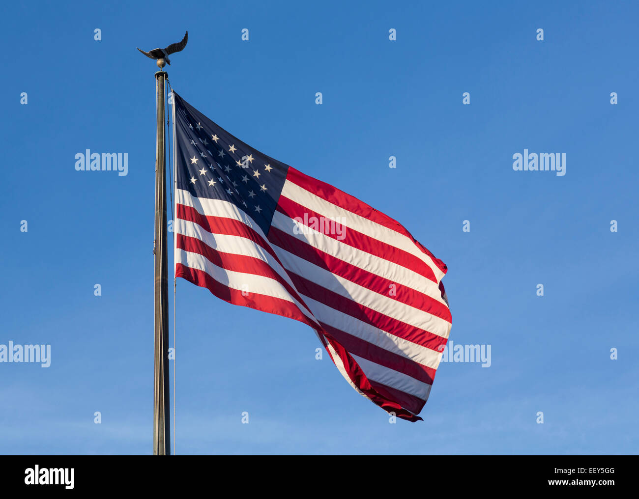 USA flag of stars and stripes with eagle flagpole against blue sky - Stock Image