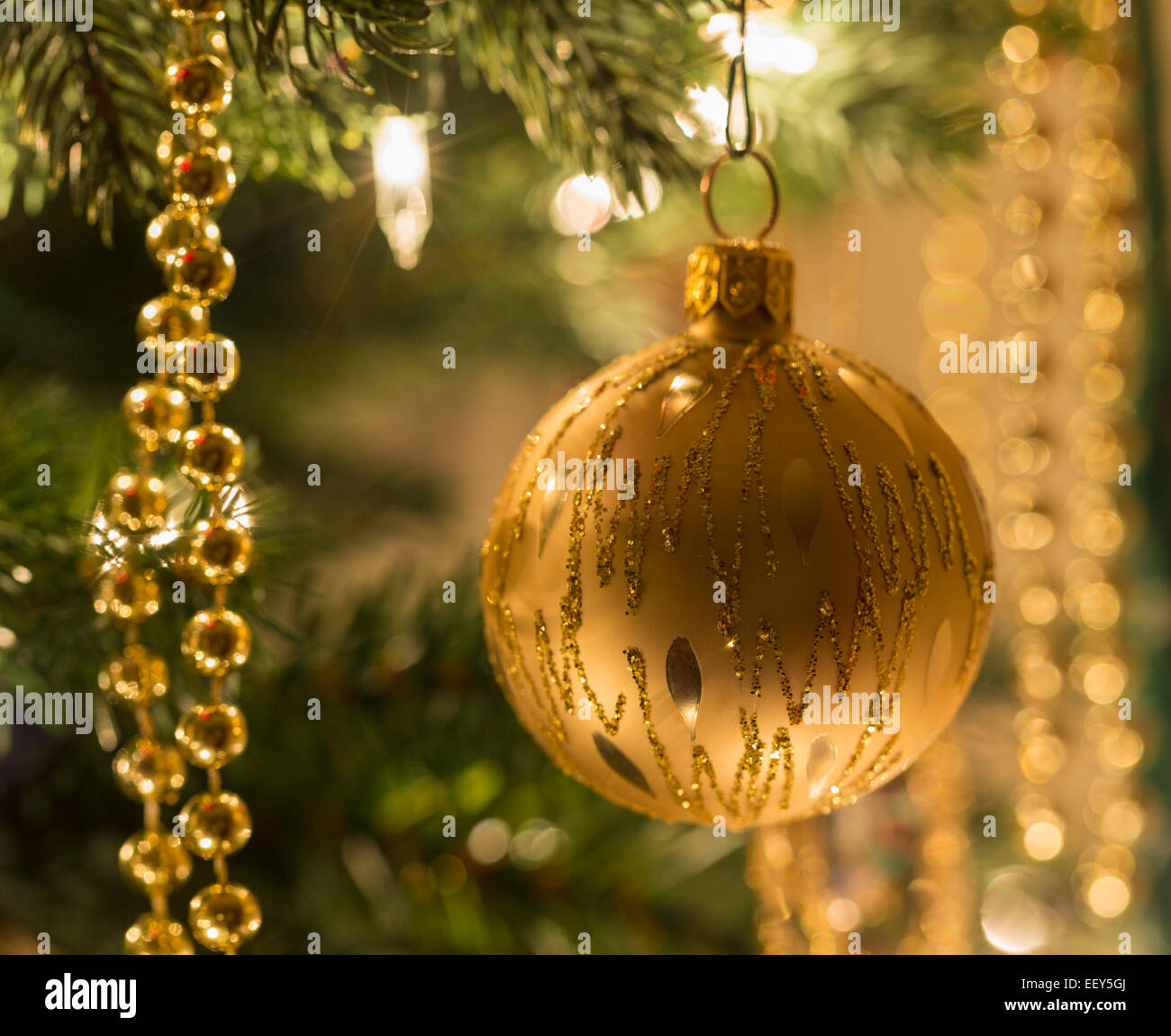 Christmas decorations on a Christmas tree illuminated by lights - Stock Image