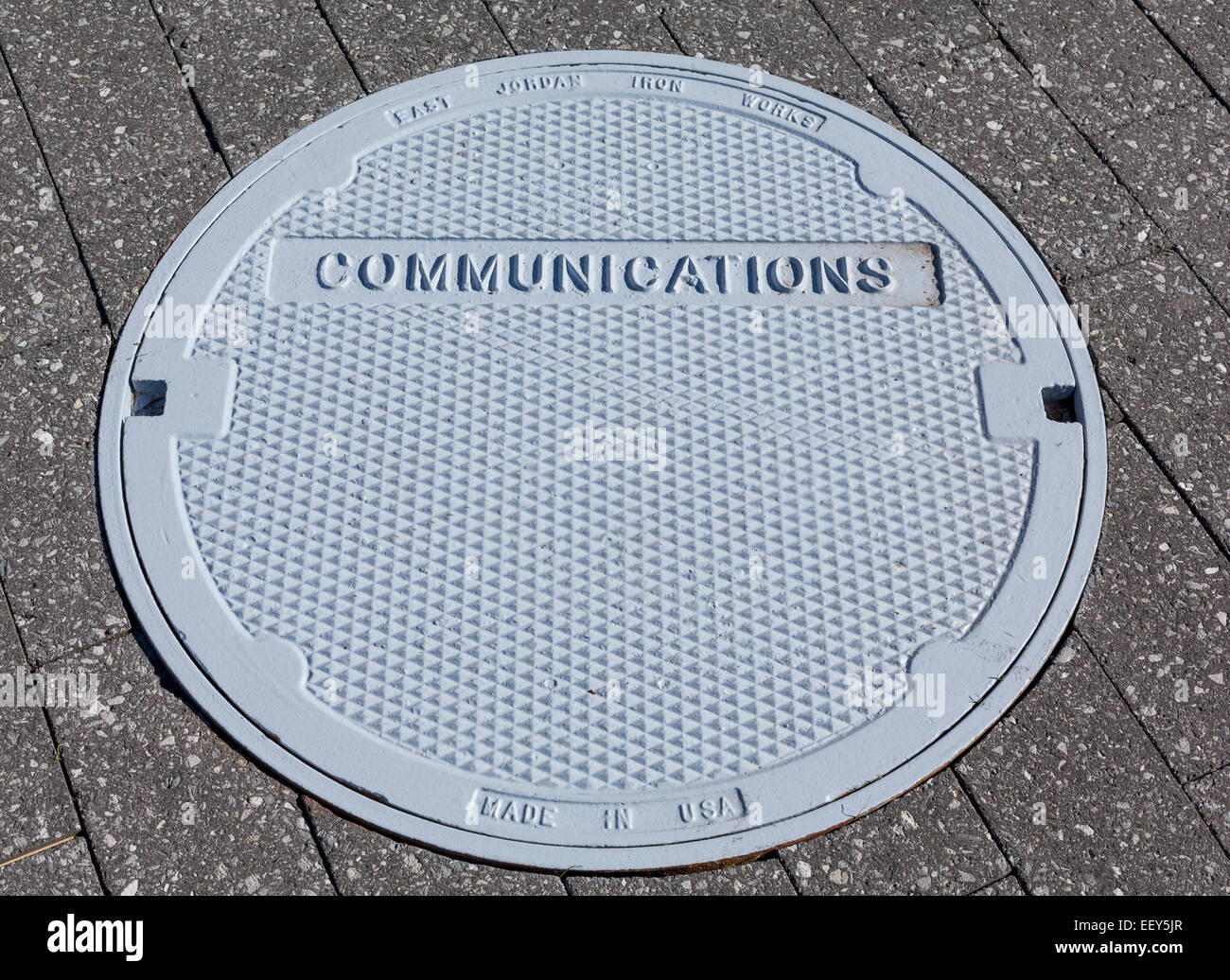 Communications manhole cover in a pavement - communication concept - Stock Image
