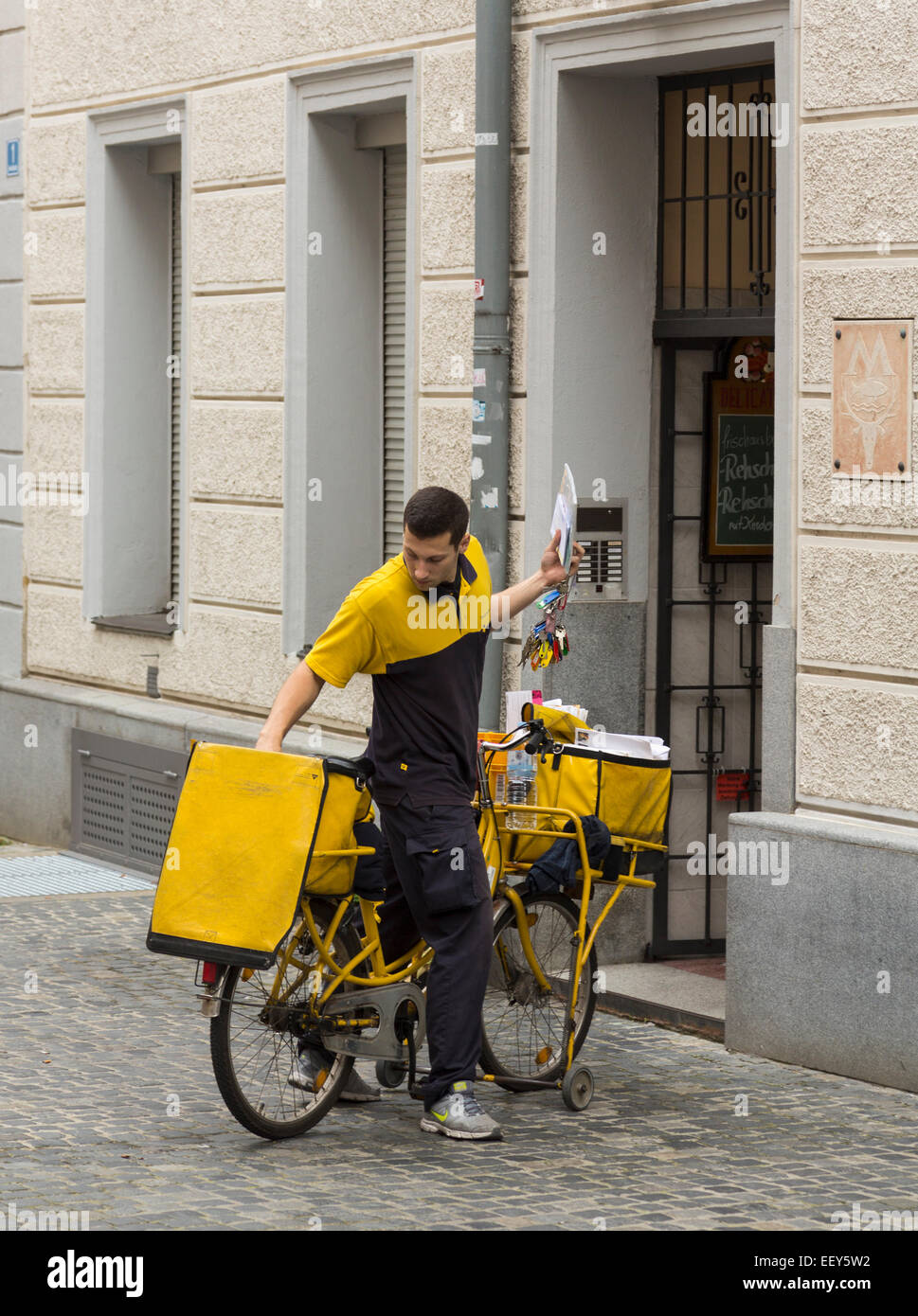 Postman delivering letters from bicycle in Regensburg, Bavaria, Germany Stock Photo