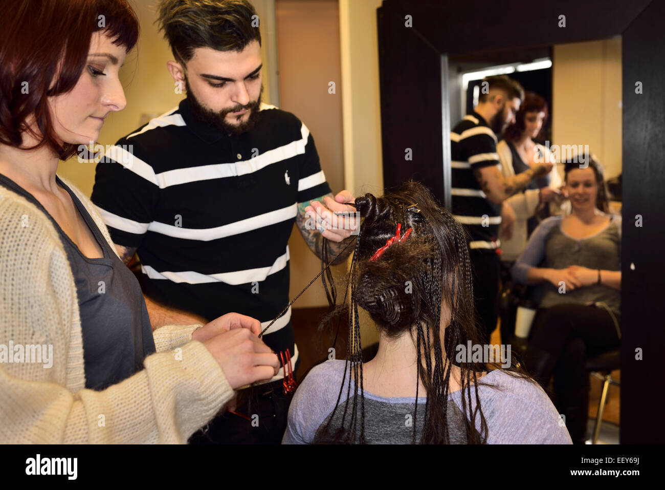 Young male and female trainee hairstylists working on braiding hair of a female customer in a salon - Stock Image