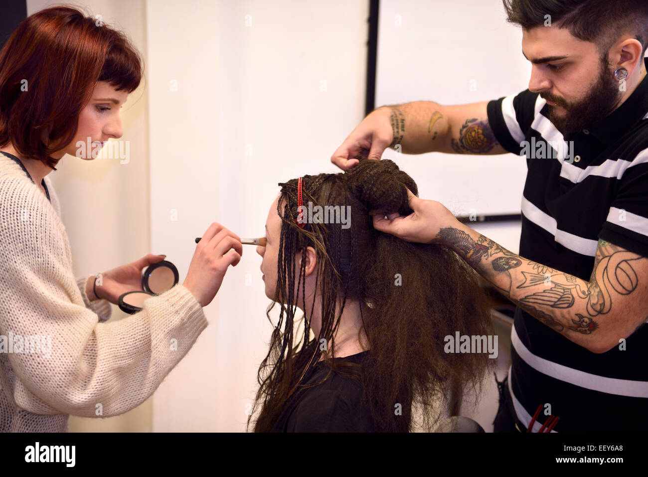 Student makeup artist and hairstylist working on braided hair with doughnut on a model - Stock Image