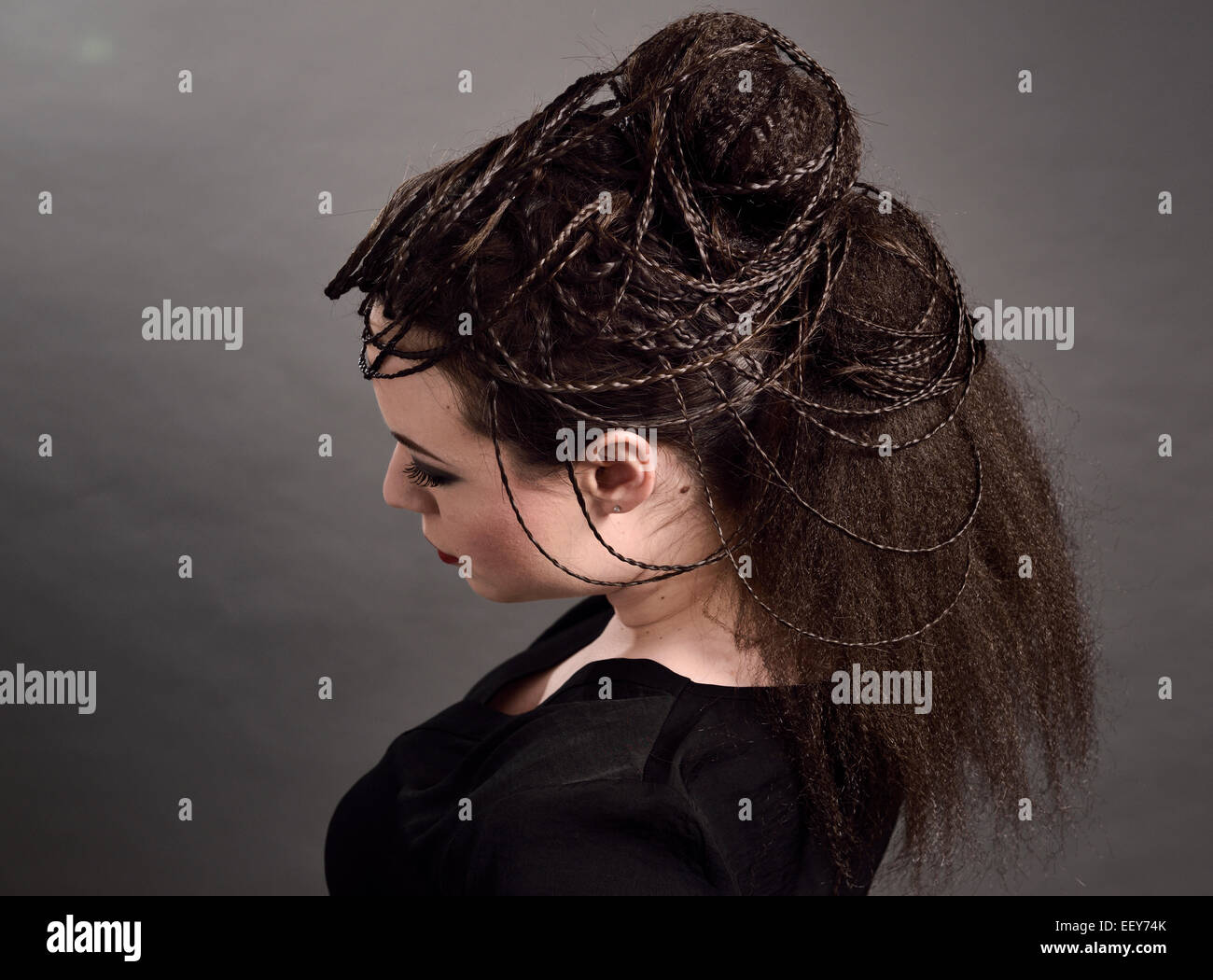Head of young female model with a rope braided updo hairstyle with crimped pony tail hair - Stock Image