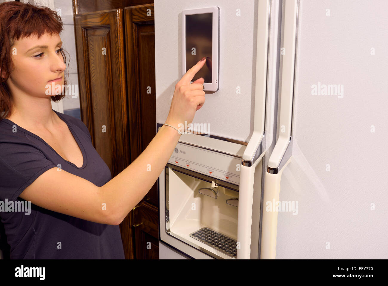 Young woman operating touch pad on web enabled refrigerator internet of things appliance in kitchen - Stock Image