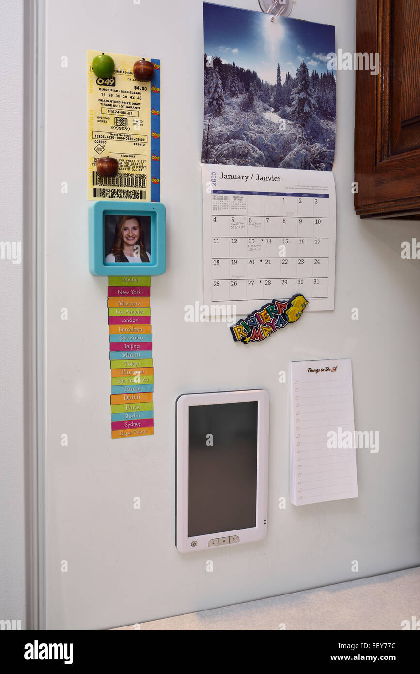 Magnet notes, calendar, lottery ticket, and web internet connectivity tablet screen on side of a refrigerator - Stock Image