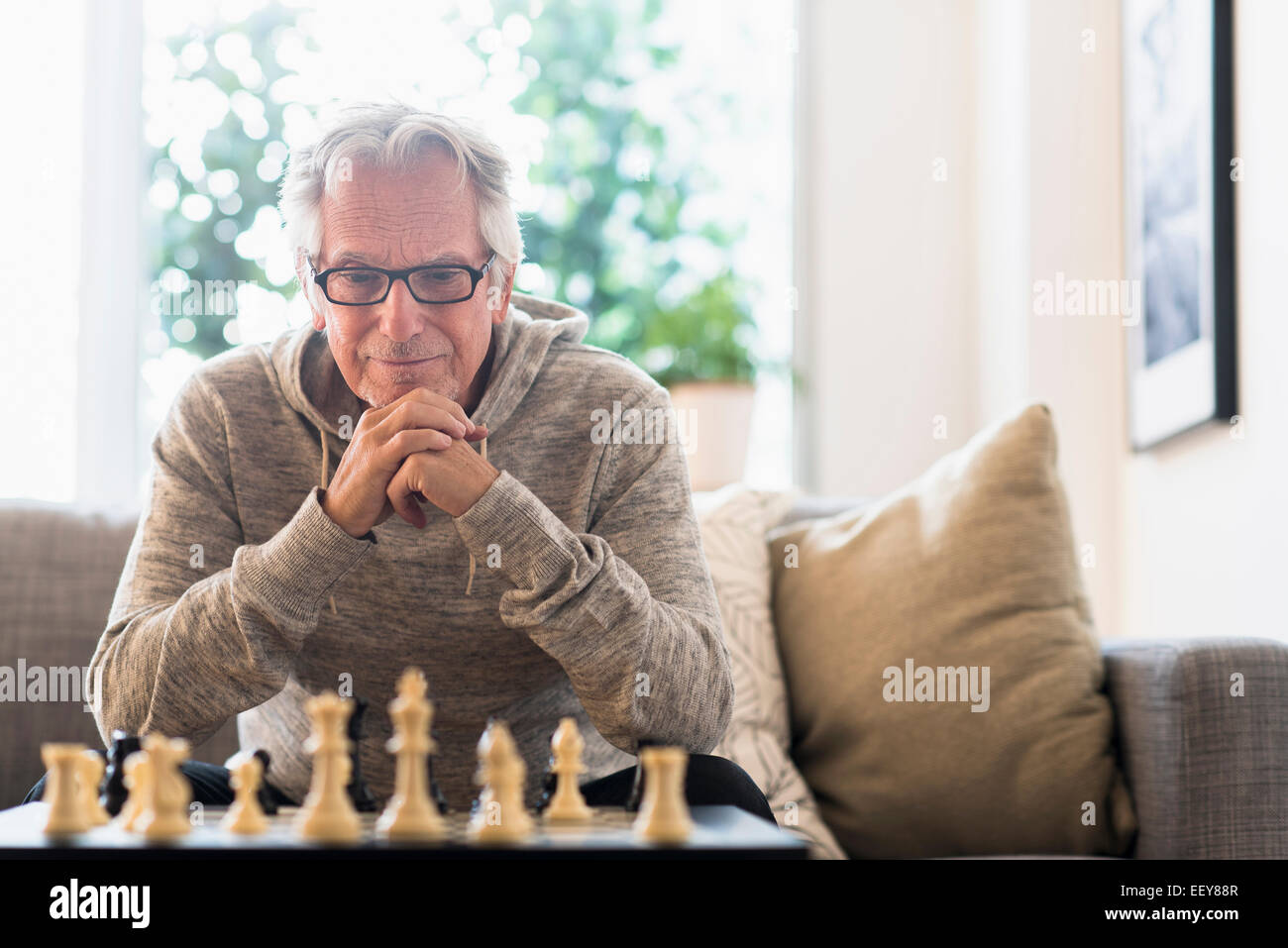 Senior man sitting in living room and playing chess - Stock Image