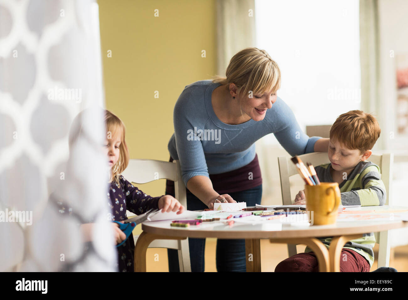 Mother playing with daughter and son (4-5, 6-7) - Stock Image