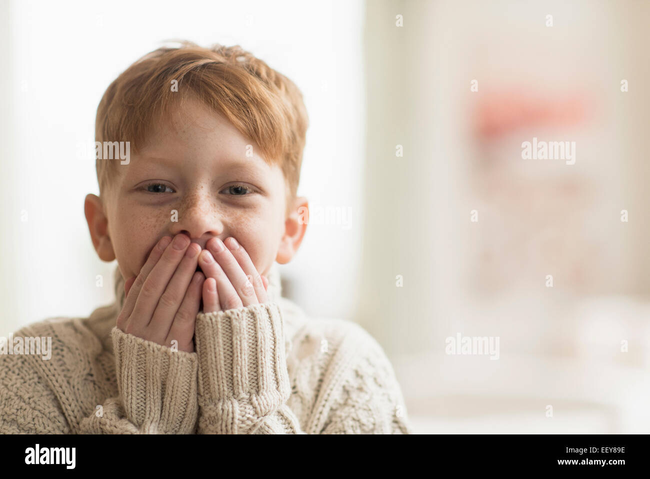Portrait of boy (6-7) with hands covering mouth Stock Photo