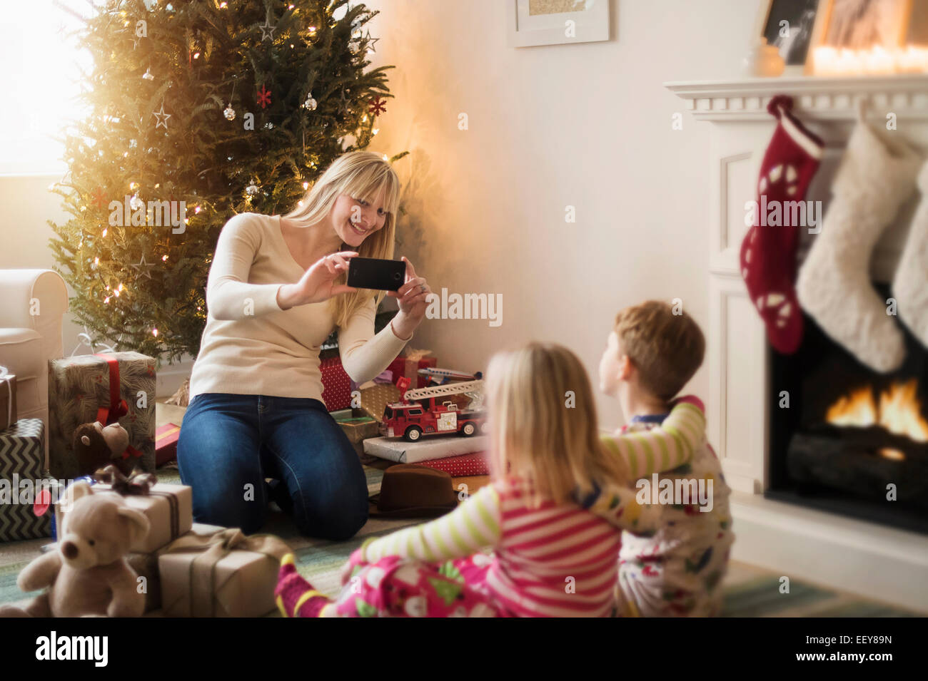 Mother with children (4-5, 6-7) opening christmas presents and taking photos - Stock Image