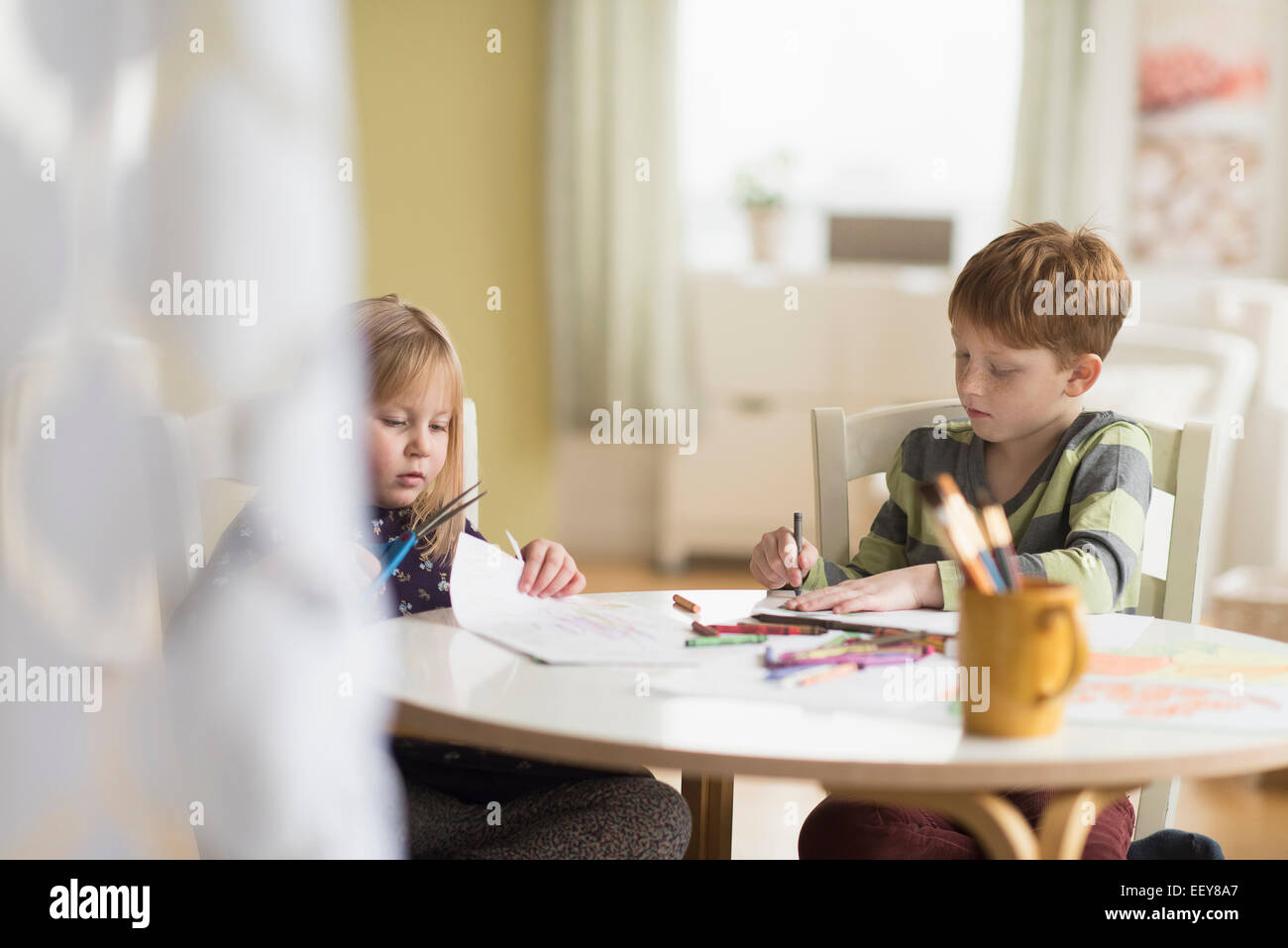 Sister and brother (4-5, 6-7) drawing in family room - Stock Image