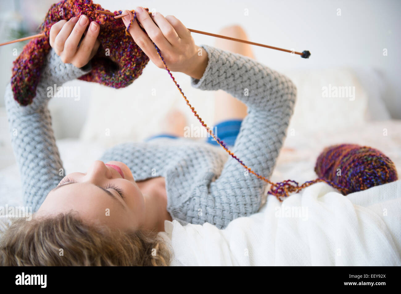 Young woman lying down and knitting - Stock Image