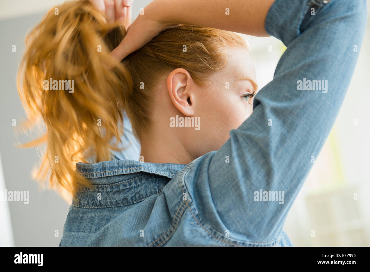 Young woman tying hair - Stock Image