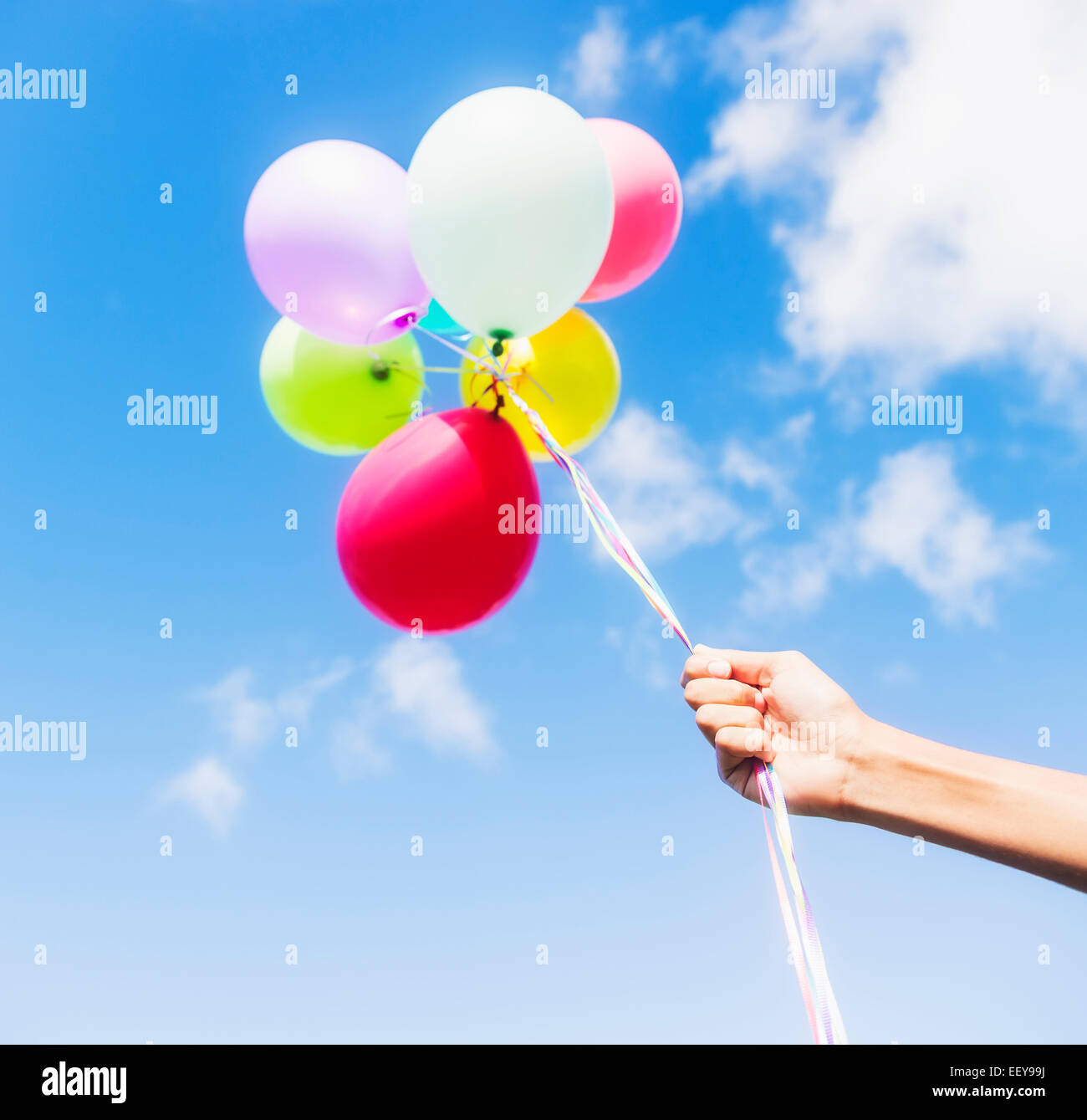 Young man holding balloons - Stock Image