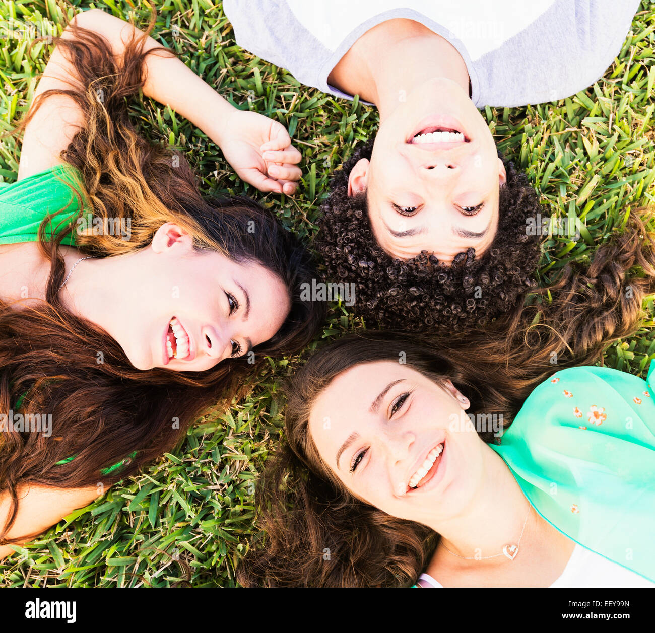 Portrait of friends (14-15) lying on grass - Stock Image