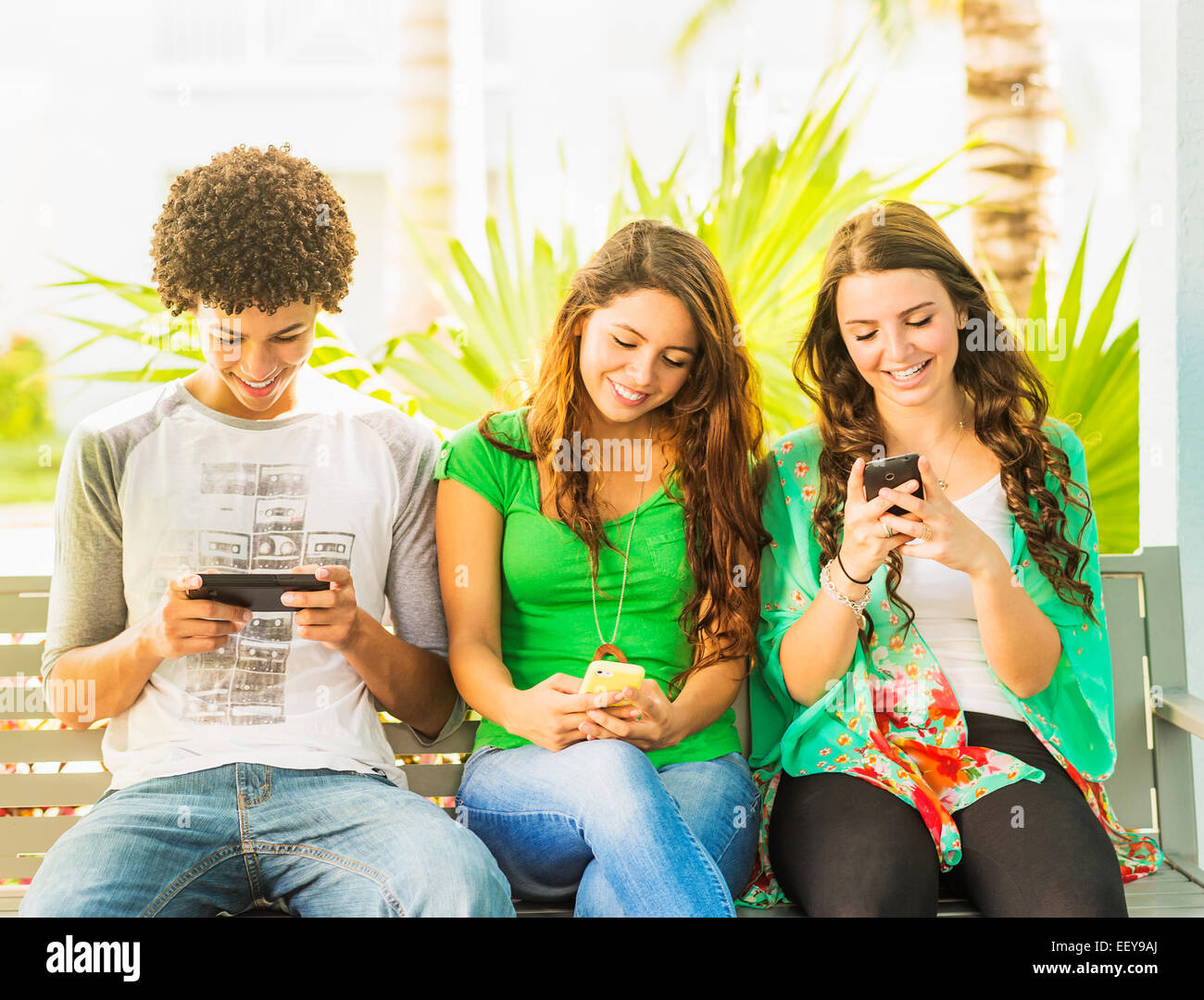 USA, Jupiter, Florida, Group of friends (14-15) sitting on bench and texting - Stock Image