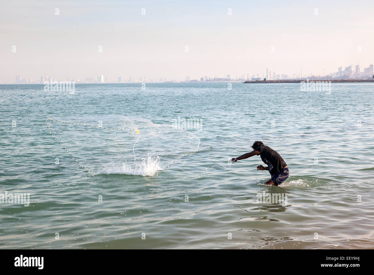 Arabic man fishes with the traditional net in the Persian