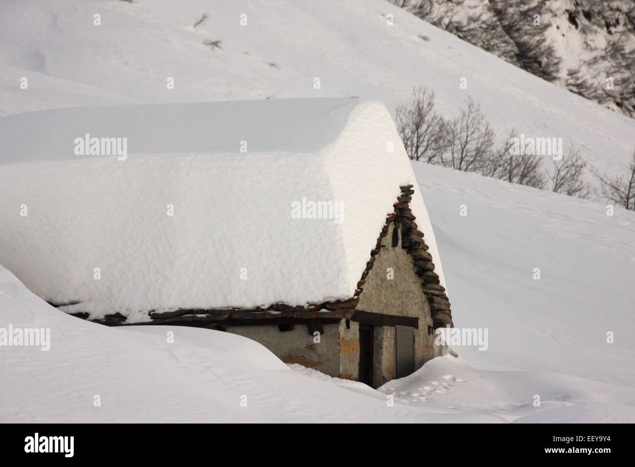 beautiful chalet house covered by snow mountain white stone - Stock Image