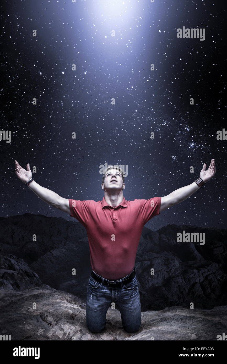 Young man knelt before a light from the sky - Stock Image