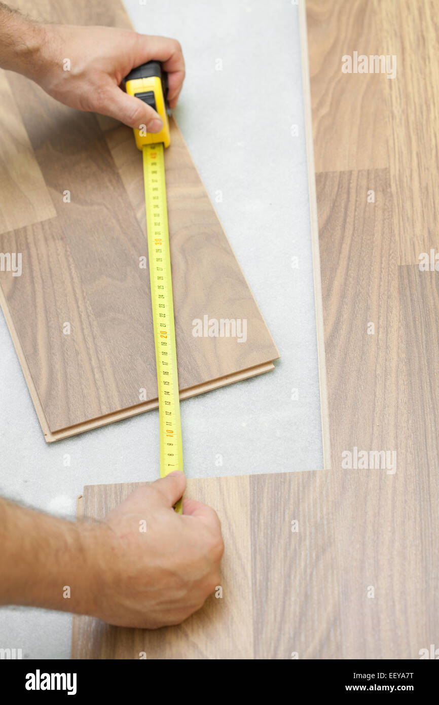 Carpenter measuring wooden floor plank - Stock Image