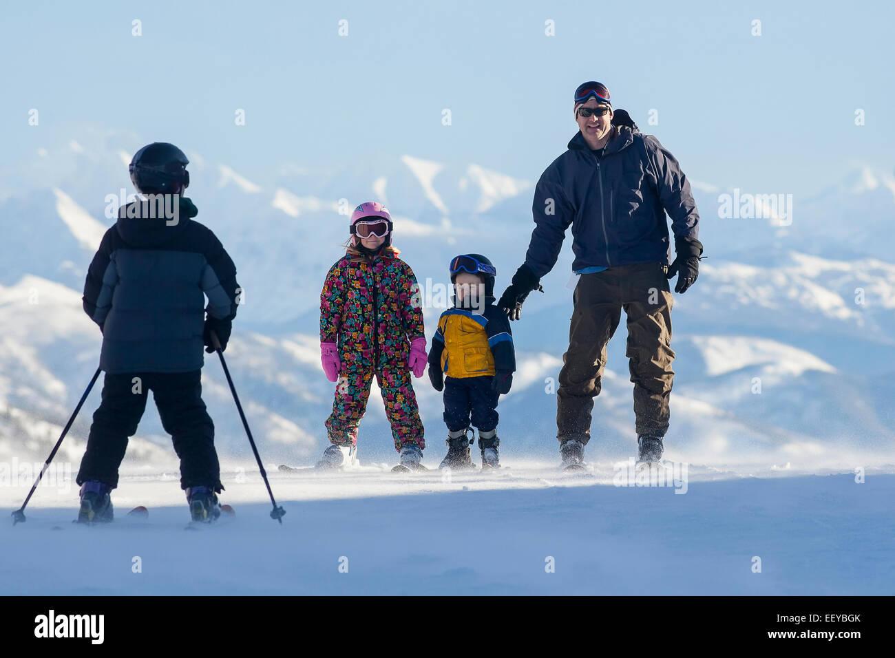 USA, Montana, Whitefish, Father skiing with children (6-7, 8-9) - Stock Image