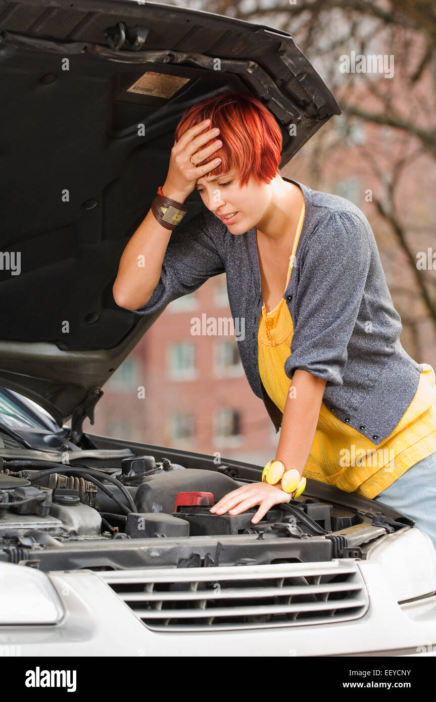 Frustrated woman looking under hood of car Stock Photo