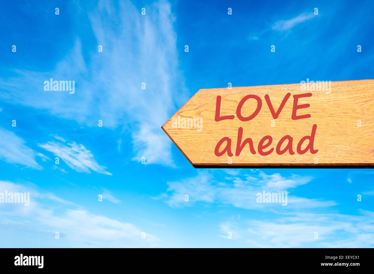 Wood arrow sign against clear blue sky with Love ahead message, Emotion and feelings concept - Stock Image